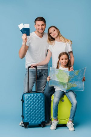 smiling parents and daughter with travel bags, map, tickets and passports on blue