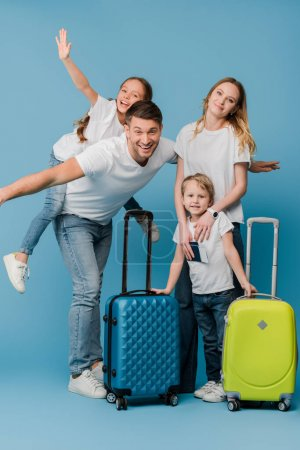 excited family of travelers with suitcases, passports and tickets on blue