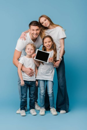 Photo for Happy family showing digital tablet with blank screen on blue - Royalty Free Image