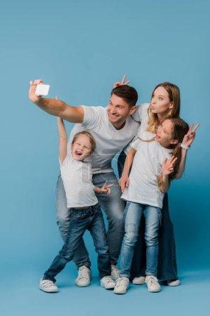 Photo pour Famille joyeuse montrant des signes de victoire tout en prenant selfie sur smartphone sur bleu - image libre de droit