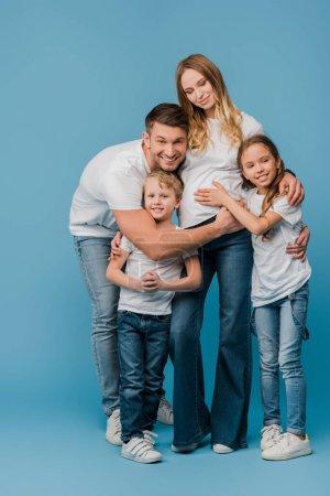 Photo pour Mari heureux et les enfants étreignant femme enceinte sur bleu - image libre de droit