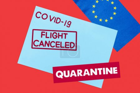 Photo for Top view of blue envelope with covid-19, flight canceled and quarantine lettering near european union flag isolated on red - Royalty Free Image