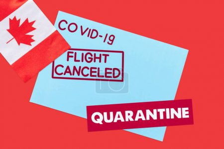 top view of blue envelope with covid-19, flight canceled and quarantine lettering near flag of canada isolated on red