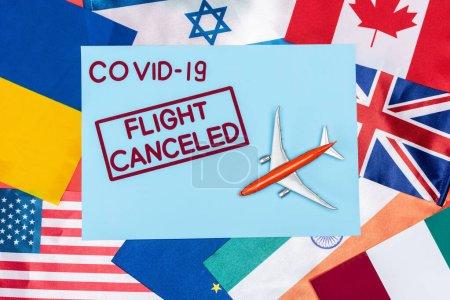 Photo pour Vue de dessus de l'enveloppe bleue avec covid-19 et vol annulé lettrage près de jouet avion sur différents drapeaux - image libre de droit