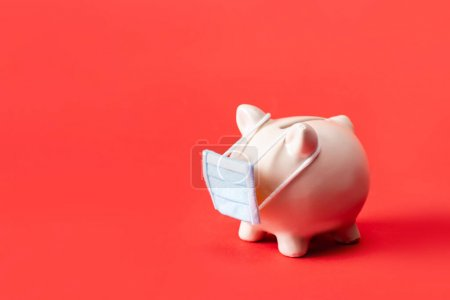 Photo for Piggy bank in small medical mask on red - Royalty Free Image