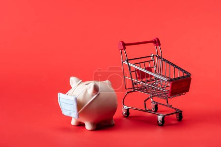 Photo for Piggy bank in small medical mask near toy shopping cart on red - Royalty Free Image