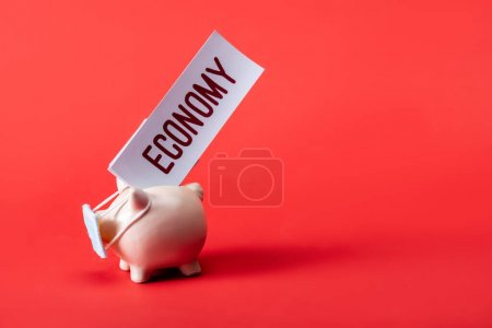 Photo for Piggy bank in medical mask near card with economy lettering on red - Royalty Free Image