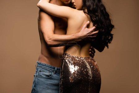 Photo pour Vue recadrée de l'homme torse nu étreignant belle petite amie à moitié nue en paillettes jupe isolée sur beige - image libre de droit