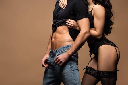 Photo pour Vue recadrée de petite amie intime en lingerie noire étreignant petit ami sexy isolé sur beige - image libre de droit