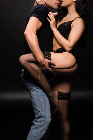 cropped view of beautiful sexy couple hugging on black