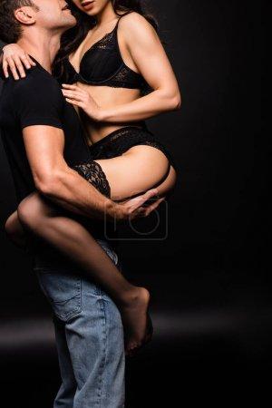 Photo pour Vue recadrée de copain tenant passionnée petite amie en lingerie noire sur les mains sur noir - image libre de droit