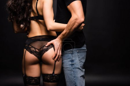 Photo for Cropped view of boyfriend holding buttocks of sexy girlfriend in black lingerie on black - Royalty Free Image