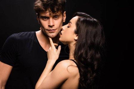 Photo pour Belle fille séduisante touchant visage de beau petit ami et va l'embrasser isolé sur noir - image libre de droit