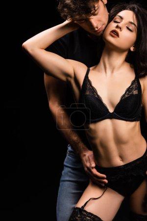 Photo pour Beau copain embrassant petite amie séduisante en lingerie noire isolée sur noir - image libre de droit