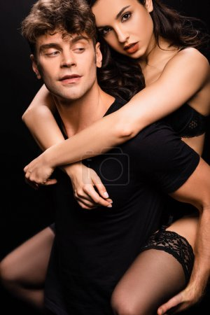 Photo for Handsome boyfriend piggybacking sexy girlfriend in black lingerie isolated on black - Royalty Free Image