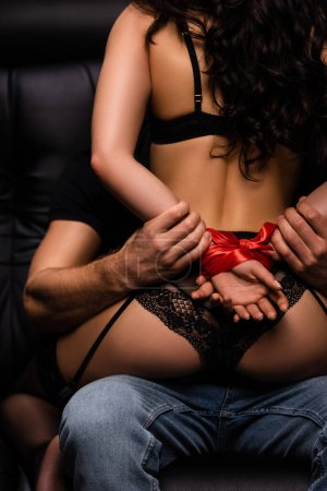 cropped view of seductive woman with bound hands with red ribbon sitting on man on black sofa