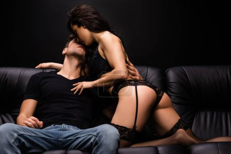 Photo for Young passionate couple hugging and going to kiss on sofa isolated on black - Royalty Free Image