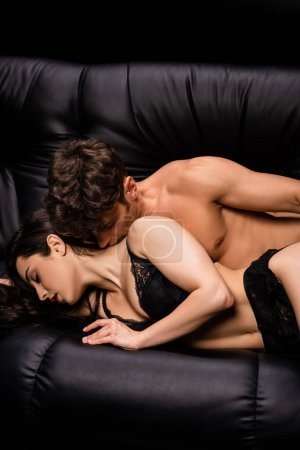 Photo for Sexy couple hugging on sofa isolated on black - Royalty Free Image