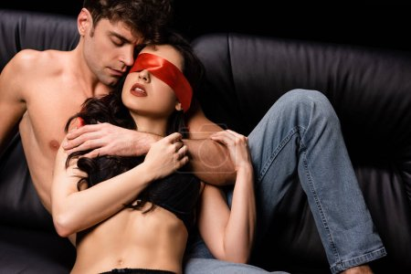 Photo for Passionate woman with red ribbon on eyes lying with shirtless man on sofa isolated on black - Royalty Free Image