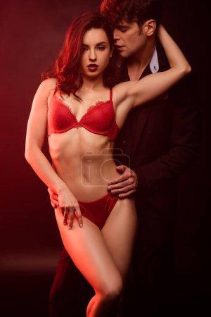 Photo pour Couple intime serrant le noir dans un feu rouge - image libre de droit