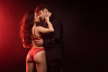 Photo for Man in suit hugging and going to kiss sexy girlfriend in red lingerie on black with red light - Royalty Free Image
