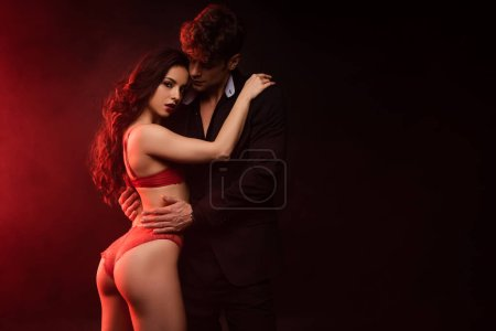 Photo for Man in suit hugging sexy girlfriend in red lingerie on black with red light - Royalty Free Image