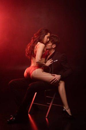Photo pour Homme passionné en costume serrant la petite amie sexy en lingerie rouge sur noir avec feu rouge - image libre de droit