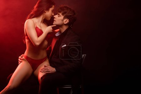 Photo for Sexy girlfriend in red lingerie going to kiss handsome man on black with red light - Royalty Free Image
