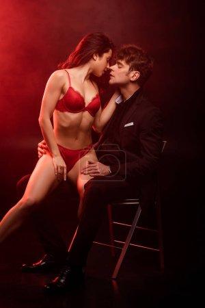 Photo pour Séduisante petite amie en lingerie rouge va embrasser bel homme sur noir avec lumière rouge - image libre de droit