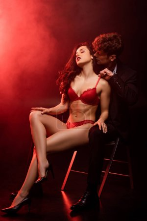 Photo pour Sexy man in suit hugging passionate woman in red lingerie on black with red light - image libre de droit