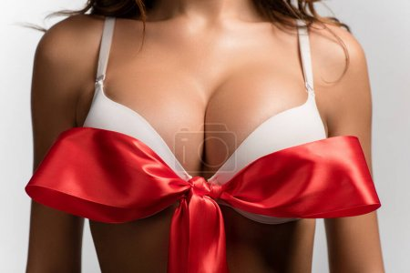 cropped view of sexy girl with big breasts and red satin bow on bra isolated on white