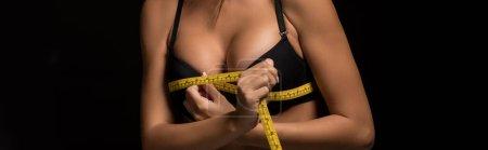 Photo pour Vue partielle de fille sexy mesurant seins avec ruban à mesurer isolé sur noir, panoramique - image libre de droit