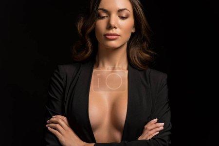 Photo pour Sensuelle, confiante fille en blazer déboutonné posant avec les bras croisés isolés sur noir - image libre de droit