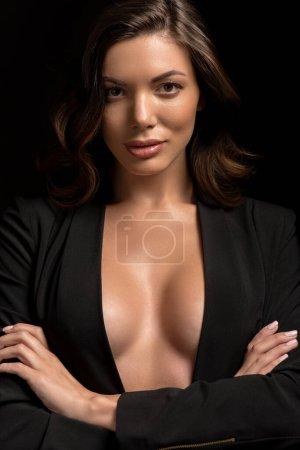Photo pour Confiante, fille séduisante dans un blazer déboutonné posant avec les bras croisés isolés sur noir - image libre de droit