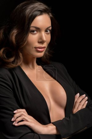 confident, sexy girl in unbuttoned blazer looking at camera while posing with crossed arms isolated on black
