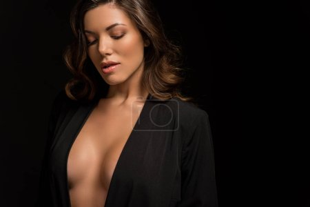dreamy, sexy girl in black unbuttoned blazer posing isolated on black