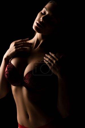 sinnliche Mädchen mit großen Brüsten in Spitzen-BH posiert mit geschlossenen Augen isoliert auf schwarz