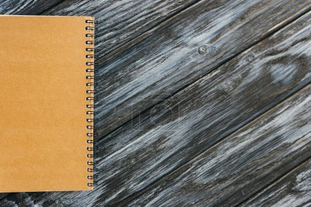 top view of notebook on dark wooden surface with copy space