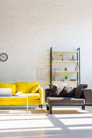 living room with yellow sofa, grey armchair, shelf and laptop in sunlight
