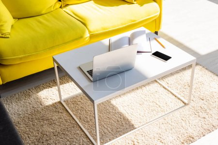 Photo for Living room with yellow sofa and table with laptop, smartphone and notepad in sunlight - Royalty Free Image