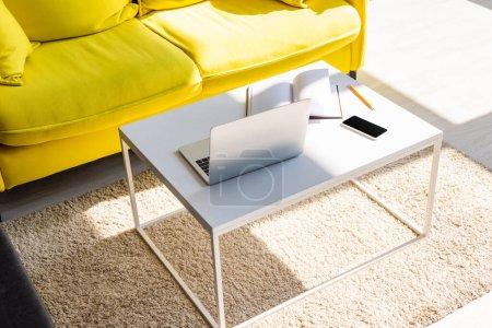 Photo pour Salon avec canapé jaune et table avec ordinateur portable, smartphone et bloc-notes à la lumière du soleil - image libre de droit