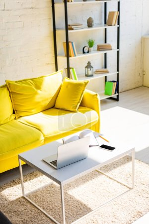 living room with yellow sofa, shelf and table with laptop, smartphone and notepad in sunlight