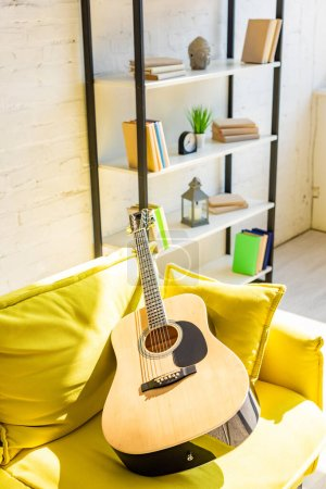 Photo for Acoustic guitar on yellow sofa in sunlight - Royalty Free Image