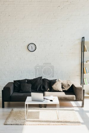 Photo for Living room with grey sofa, shelf and table with laptop in sunlight - Royalty Free Image