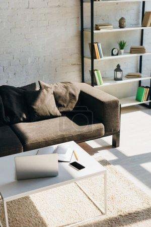 Wohnzimmer mit grauem Sofa, Regal und Tisch mit Laptop, Smartphone und Notizblock im Sonnenlicht