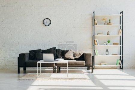 Wohnzimmer mit grauem Sofa, Uhr, Regal und Tisch mit Laptop im Sonnenlicht
