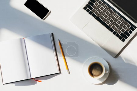 Photo for Top view of empty workplace with laptop, smartphone, notepad, pencil and cup of coffee in sunlight - Royalty Free Image