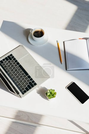 Photo for Workplace with laptop, smartphone, notepad and coffee cup in sunlight - Royalty Free Image