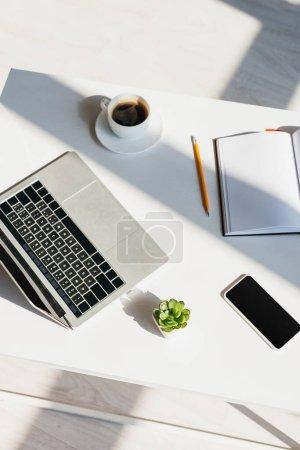 Photo pour Lieu de travail avec ordinateur portable, téléphone intelligent, bloc-notes et tasse à café au soleil - image libre de droit