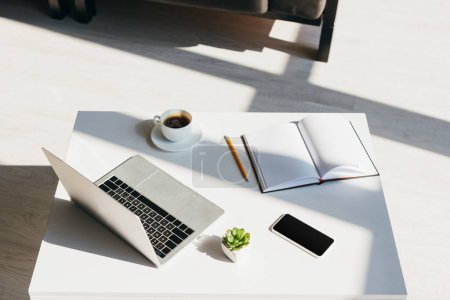Photo for Empty workplace with laptop, smartphone, notepad and cup of coffee in sunlight - Royalty Free Image